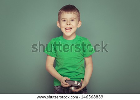Cheerful smiling child (boy) holding a instant camera - stock photo