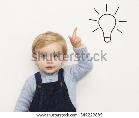 Cheerful smiling child pointing up on white background