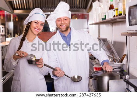 Cheerful smiling cooks working together at kitchen in take-away restaurant  - stock photo