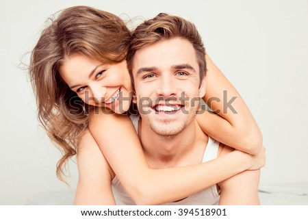 Cheerful smiling couple in love hugging in the bedroom - stock photo