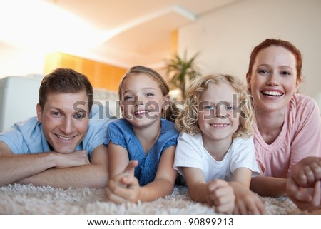 Cheerful smiling family on the carpet - stock photo