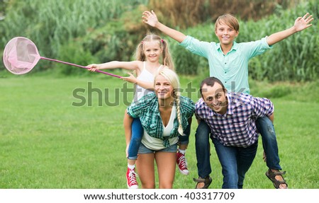 Cheerful smiling family with two children spending weekend at the lawn in countryside  - stock photo