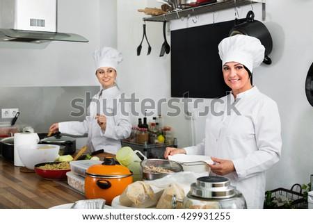 Cheerful  smiling female chefs preparing food on restaurant kitchen - stock photo
