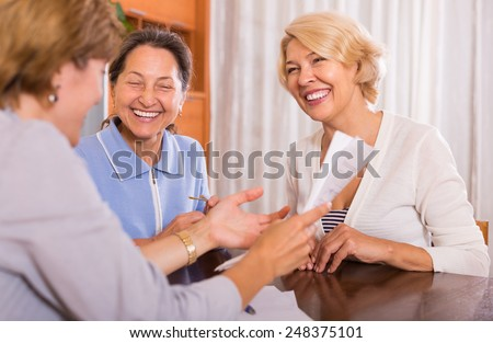 Cheerful smiling female pensioners taking legal advice from public notary - stock photo