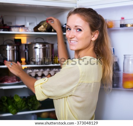 Cheerful smiling girl searching for something in refrigerator