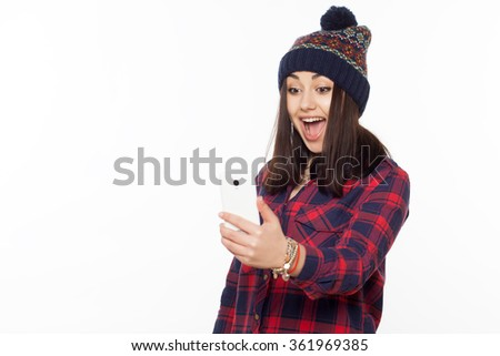 Cheerful smiling girl wearing a hat taking a self portrait with a cell phone. Front portrait isolated on white. - stock photo