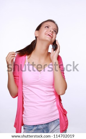 Cheerful smiling girl with mobile in period of conversation
