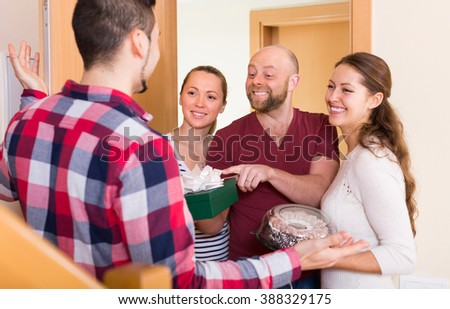 Cheerful smiling guests with gifts in hands standing in doorway. Focus on man