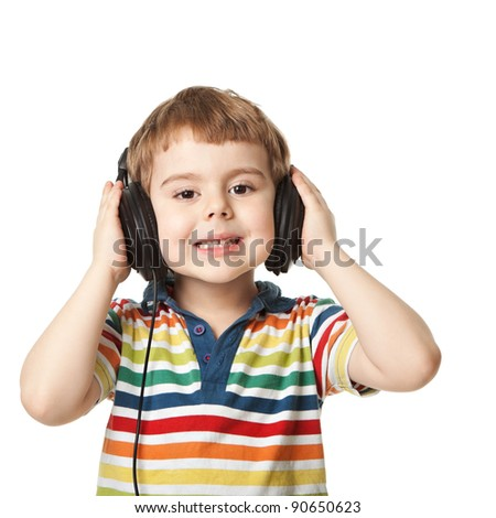 cheerful smiling little boy  listening to music in headphones. Isolated on white background.  shooting in the studio - stock photo