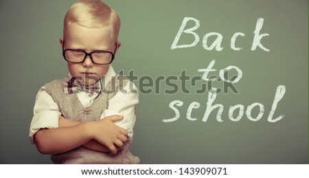 Cheerful smiling little boy on a green background. Looking at camera. School concept