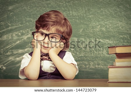 Cheerful smiling little boy sitting at the table. Looking at camera School concept - stock photo