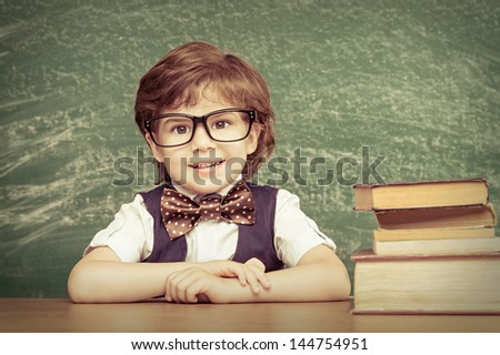 Cheerful smiling little boy sitting at the table. Looking at camera School concept