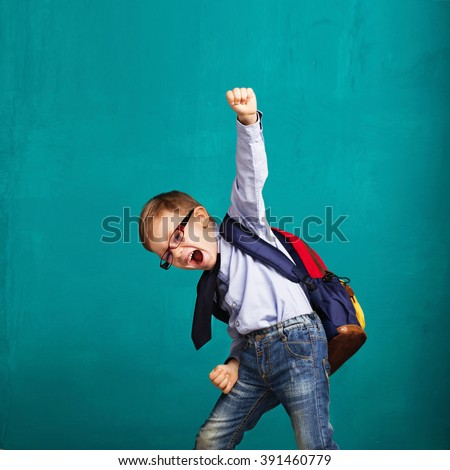 Cheerful smiling little boy with big backpack jumping and having fun against blue wall. Looking at camera. School concept. Back to School