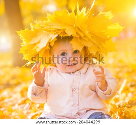 cheerful smiling little girl among autumn maple leaves - stock photo