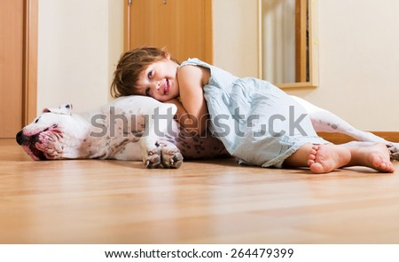 Cheerful smiling little girl hugging big white dog at home  - stock photo