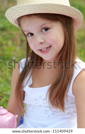 Cheerful smiling little girl in a white dress walks in the summer the park on a sunny summer day