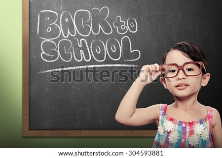 Cheerful smiling little girl on chalkboard background. Looking at camera. Back to school concept