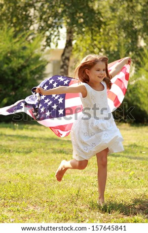 Cheerful smiling little girl running on the field with an American flag