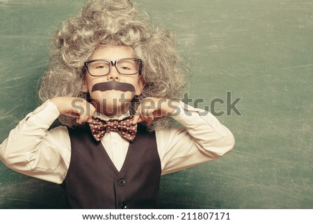 Cheerful smiling little kid (boy) against chalkboard. Looking at camera. Little genius style. School concept - stock photo