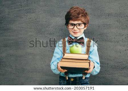 Cheerful smiling little kid (boy) against chalkboard. Looking at camera. School concept - stock photo