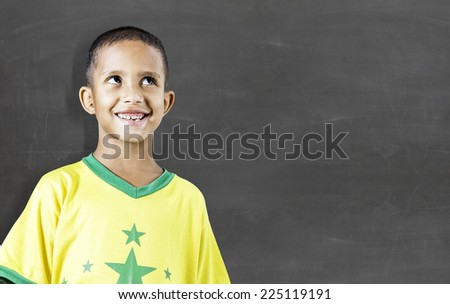 Cheerful smiling little kid (boy) against chalkboard. School concept - stock photo