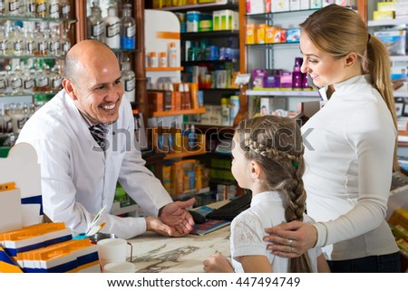 Cheerful smiling male pharmacist wearing white coat standing at the counter in pharmacy  - stock photo