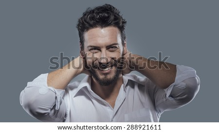 Cheerful smiling man relaxing with hands behind head - stock photo