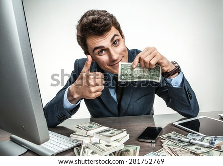 Cheerful smiling man showing thumbs up success sign / modern businessman at his desk with computer and a lot of money - stock photo