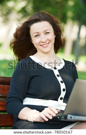 cheerful smiling middle age woman working on a laptop computer outdoors