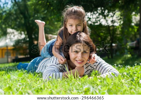 Cheerful Smiling Mother and Daughter playing on Green Grass in Summer Day - stock photo