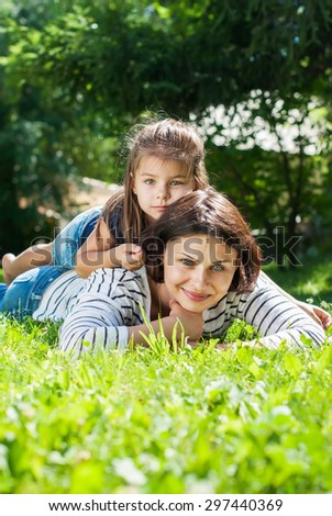 Cheerful Smiling Mother and Daughter playing on Green Grass in Summer Day
