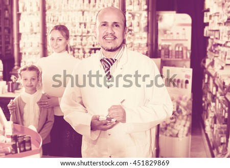 cheerful smiling pharmacist 40-50 years old helping customers - stock photo