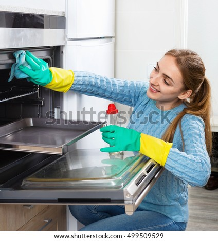 Cheerful smiling positive adult girl in gloves removing snuff in oven