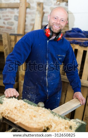 Cheerful smiling professional worker working on a machine at wood workshop  - stock photo