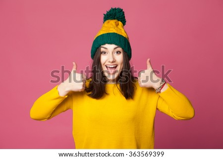 Cheerful smiling stylish young girl wearing warm yellow clothes and hat, showing thumbs up against the pink wall