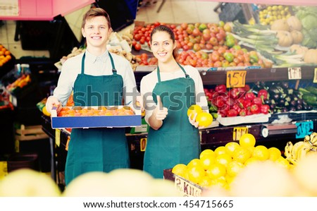 Cheerful smiling supermarket workers in fruit and vegetables section  - stock photo