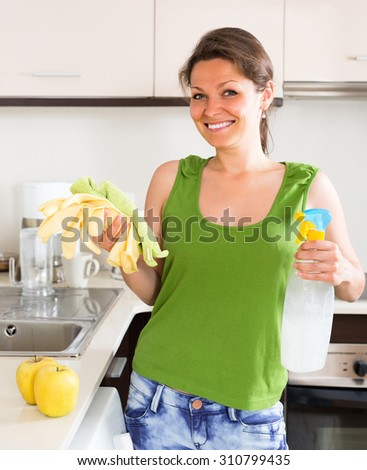 Cheerful smiling woman cleaning furniture in kitchen at home