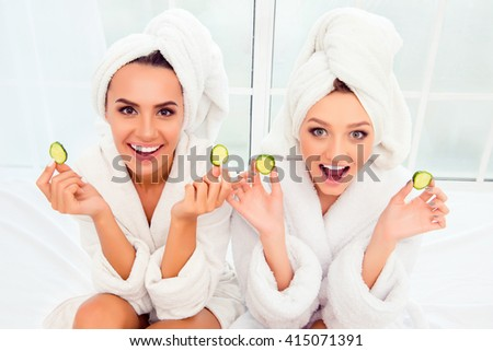 Cheerful smiling woman in bathrobes and towelson their heads holding slices of cucumber - stock photo