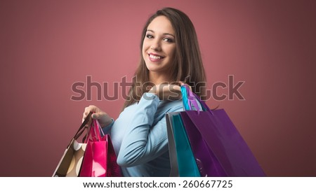 Cheerful smiling woman shopping with lots of colorful bags - stock photo