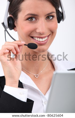 Cheerful, smiling woman with a headset and laptop - stock photo