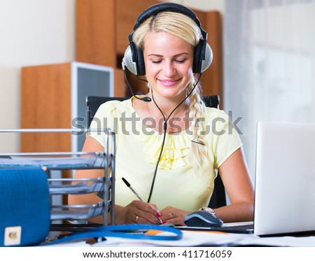 Cheerful smiling young blonde woman with headset working at laptop  - stock photo