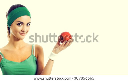 Cheerful smiling young brunette woman in green fitness wear with apple, with blank copyspace area for slogan or text - stock photo