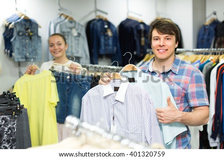 Cheerful smiling young couple during shopping at the clothing store. Focus on guy - stock photo