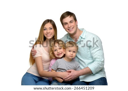 Cheerful smiling young family of four enjoying time together and looking at camera. Isolated on white background. Concept for happy family - stock photo