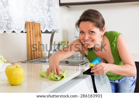 Cheerful smiling young housewife cleaning furniture with rag at home kitchen - stock photo