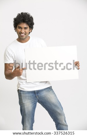 Cheerful smiling young Indian man holding a blank billboard on white background - stock photo