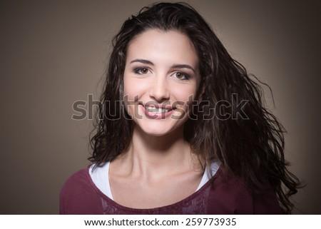 Cheerful smiling young woman looking at camera - stock photo