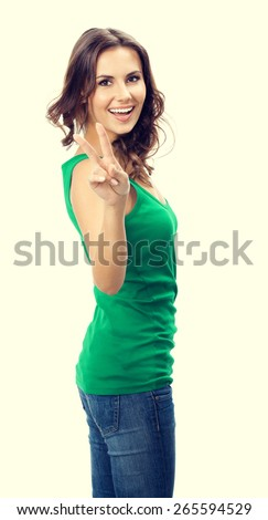 Cheerful smiling young woman showing two fingers or victory gesture, in smart green casual clothing - stock photo