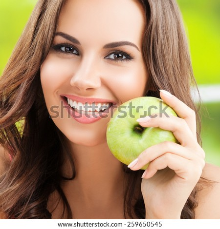 Cheerful smiling young woman with green apple, outdoor - stock photo