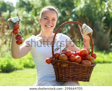 Cheerful smiling young woman with tomato harvest in garden - stock photo